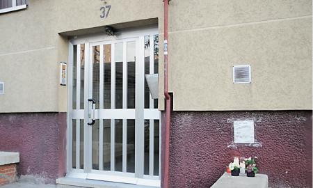Velas y flores en la portería del edificio y un cartel: «Juan Luis tus amigos no te olvidaremos»