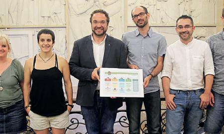 Els vuit membres de l'equip de govern municipal al vestíbul de l'Ajuntament mostrant la configuració del nou cartipàs municipal