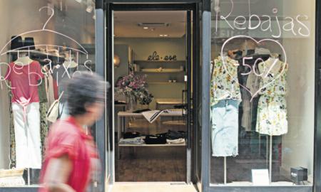 Una dona mira l'aparador d'una botiga al centre de Sabadell, amb cartells de rebaixes