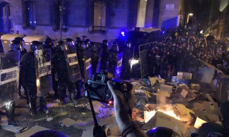 Agents de policia davant d'una foguera que comença a cremar a l'entorn de la delegació del govern espanyol a Barcelona el 15 d'octubre del 2019. Pla general. (Horitzontal)