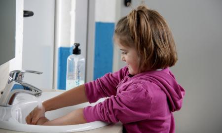 Una nena en un casal d'estiu rentant-se les mans / Albert Lijarcio (ACN)
