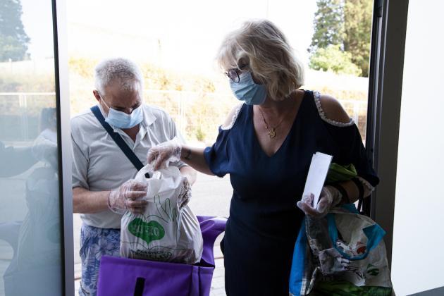 Una parella recollint un lot d'aliments del Rebost Solidari / Victòria Rovira