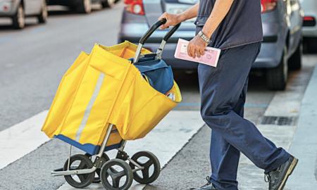 Un carter repartint paquets de Correus en un carrer del centre de la ciutat
