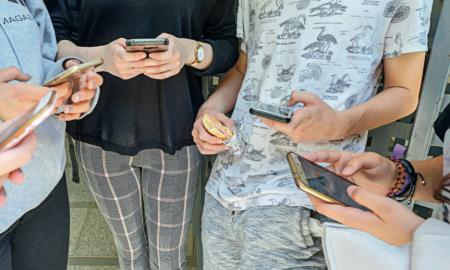 Estudiants consulten els seus telèfons mòbils mentre estan a la porta de l'Institut Vallès de Sabadell a l'hora del pati ahir al matí