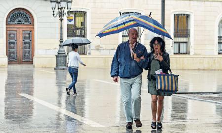 Una parella passeja sota la pluja a la Plaça de Sant Roc