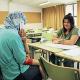Una dona amb el seu fill s'informa per estudiar castellà