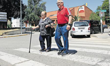 El president de l'associació de veïns de Torre-romeu, Manuel Moya creuant amb una veïna la cruïlla del carrer Sau